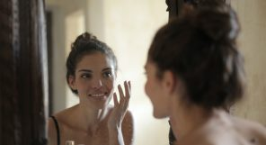 Smiling woman looking at face through mirror
