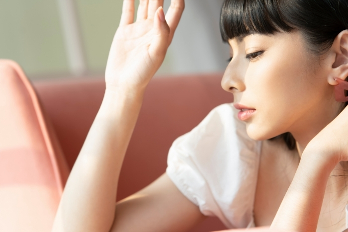 asian woman blocking sunlight from her face